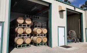 Wine barrels on racks in the barrel room at Wolff Vineyards